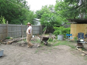 EJ putting in raised beds where the shed was. The woodshed is to the right.