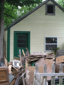 I painted some of the green trim on the garage. In front of the garage is the pile of junk I hauled out of the basement.
